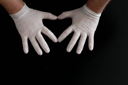 Two hands in medical gloves show heart shape on black background Standard-Bild