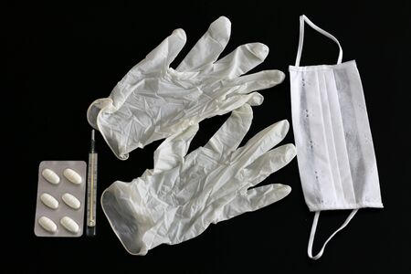 Two latex gloves, thermometer, tablets and medical mask on black background Standard-Bild