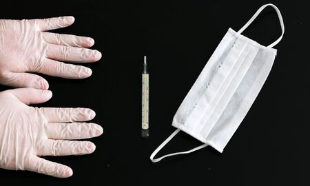 Two hands in latex gloves, thermometer and medical mask close-up on black background Standard-Bild