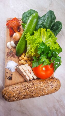 Healthy vegan products and fresh vegetables on a cutting board
