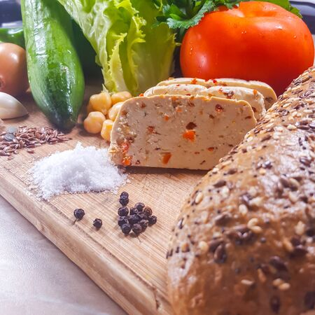 Salad, vegetables, tofu, spices and bread with seeds on a cutting board Standard-Bild