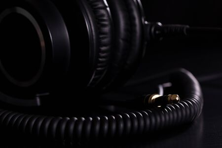 Macro details of black leather headphones on black background
