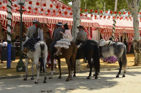 Seville, Spain, April 21, 2013: Riders on horseback walking through the fairgrounds in Seville fair