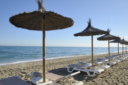 loungers: Sun loungers and straw shade umbrellas on the beach of Marbella,  Spain