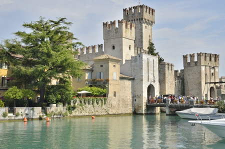 sirmione: Tourists visiting the Scaliger Castle at Sirmione on lake Grada, Italy. The Castle was built in the 13th century.  This is a rare example of medieval port fortification, which was used by the Scaliger fleet.
