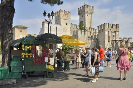 sirmione: Tourists visiting Sirmione on lake Garda, Italy. with views to the Scaliger castle, built in the 13th century.  This is a rare example of medieval port fortification, which was used by the Scaliger fleet.