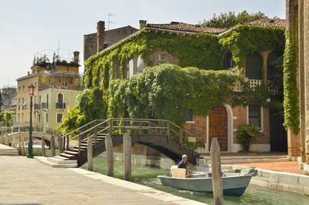 sestiere: A man in a boat navigating by a small canal in the Dorsoduro sestiere of the Italian city of Venice.