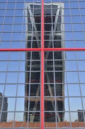 One of the twin Kio towers reflected on another one.  The towers are office buildings in Madrid, Spain .They were designed by the American architects Philip Johnson and John Burgee, commissioned by the Kuwait Investment Office (hence their initial name T