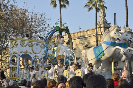 melchior: The Cavalcade of Magi, traditional parade of kings coaches in street, in Seville, Spain. The Magi (Melchior, Gaspar, and Baltasar) ride through the streets, as their page boys throw candies to children.