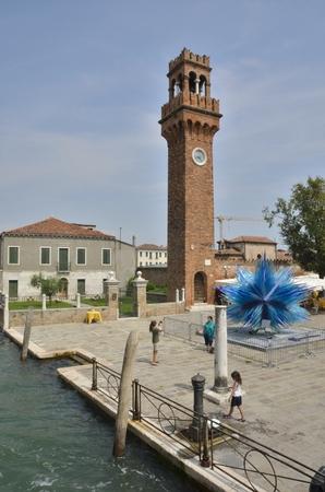 Murano: Clock tower and a blue murano glass sculpture  in Murano, Venice, Italy.