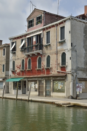 disrepair: Facade of building in disrepair on  a canal in Murano, an island in the Venetian Lagoon, northern Italy.