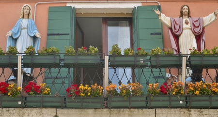 crist: Balcony with figures of Crist and the Virgin of a house of Burano, small fisher village in Venice lagoon.