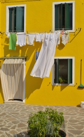 Laundry hanging on yellow  house in Burano, an island of the Venetian lagoon, Italy Stock fotó