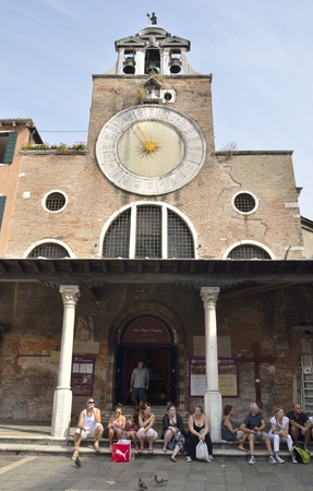 distric: People sitting in front of San Giacomo di Rialto church in the distric of San Polo, Venice, northern Italy.