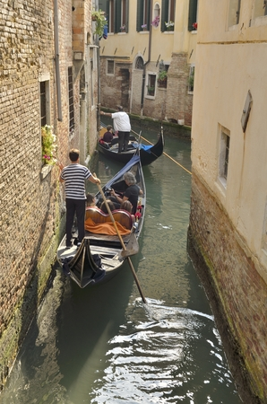 maneuver: Gondolas with tourists strolling along a narrow canal in Venice, Italy