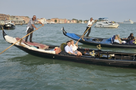 stroll: A stroll of gondolas with tourists by the Grand Canal, Venice, Italy