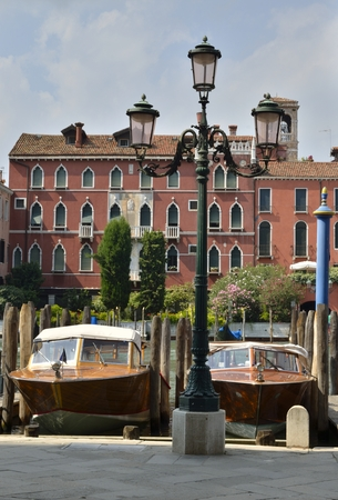 Wooden boats parkes in  a canal in Venice, Northern Italy.
