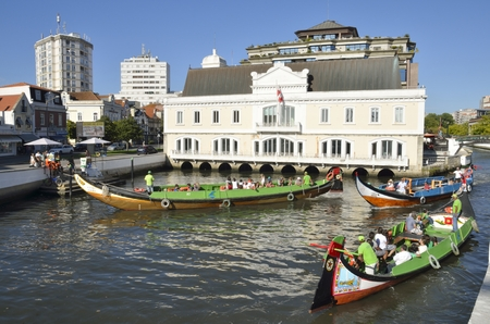 navigating: People in traditional boats navigating the waters surrounding Aveiro, in Portugal