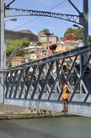 luis: Young men jumping from the bridge Dom Luis over the Douro River in Porto, Portugal.