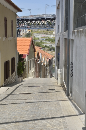 other side: Narrow street with views to the top of Dom Luis  Bridge in Gaia, located south of the city of Porto on the other side of the Douro River, Portugal. Editorial