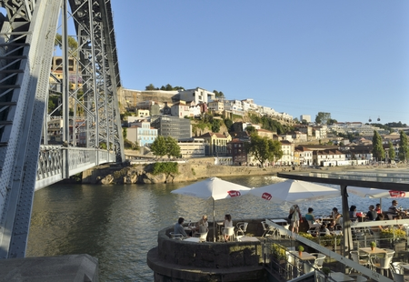 luis: People in a restaurant at the riverbanks of the Douro river next to Don Luis Bridge in Porto, Portugal.