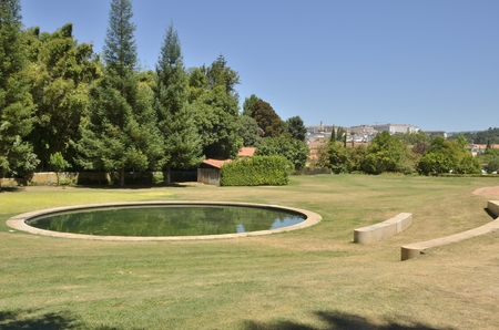 quinta: Stone seats around pond in the gardens of Quinta das Lagrimas with views to the city in Coimbra, Portugal