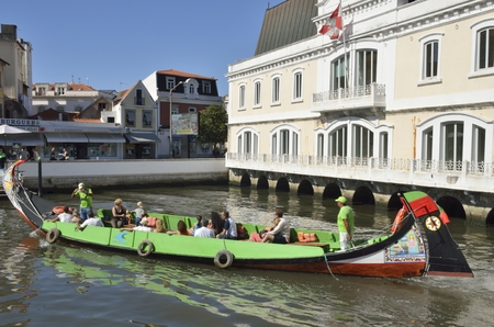 navigating: People in traditional boat navigating the waters surrounding Aveiro, in Portugal