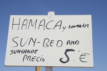 announcing: Sign announcing sun shade and sun bed in the beach of Marbella, Spain Stock Photo