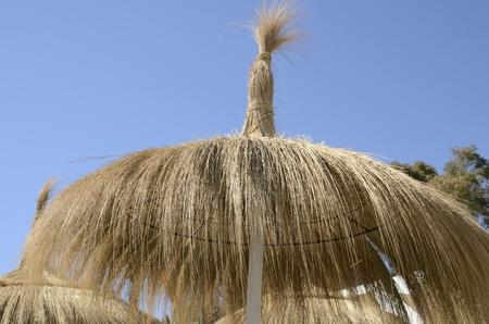 the sun and shade: Straw sun shade  on the beach of Marbella,  Spain. Stock Photo