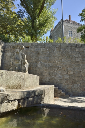 guimaraes: Medieval fountain on wall in front of the Palace of the Dukes of Braganza  in Guimaraes, Portugal.