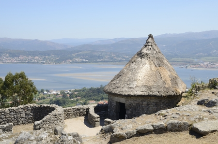 One of the reconstructed houses in the remains of a celtic settlement in Santa Tecla Mount in Galicia, Spain with views to the MInho Estuary. Stock Photo