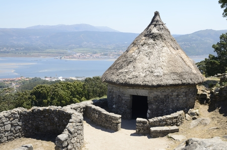 castro: Prehistoric reconstructed house in the remains of a celtic settlement in Santa Tecla Mountain with views to Minho estuary  in Galicia, Spain. Stock Photo
