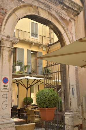 porch scene: Restaurant in patio behind a stone arch in  the city of Verona, Italy Editorial
