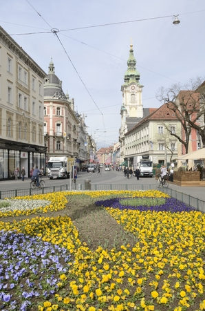 Foreground of colorful flowers  at the main street of  Graz, the capital of Styria.