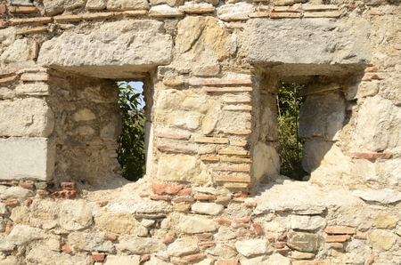 Narrow vertical apertures on  historical walls in the  medieval city of Girona, Catalonia, Spain