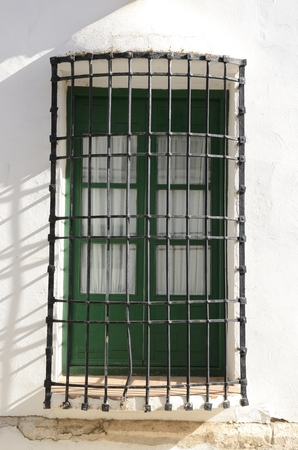 Grille on window on white house  in the village of Belmonte, province of Cuenca, Spain.