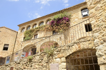 Beautiful stone house with flowers on its wall in the medieval village of Pals, located in the middle of the Emporda region of Girona, Catalonia, Spain.