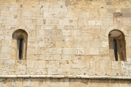 Narrow apertures of light on facade of  the monastery of Sant Pere in Besalu, a medieval town of Girona, Catalonia, Spain. Stock Photo