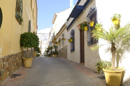 Typical Andalusian street ornamented with yellow plants pots in the village of Estepona, a town of the province of Malaga, Spain.