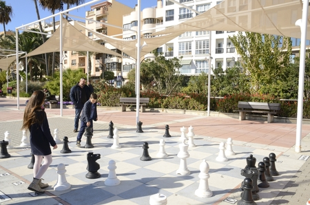 Children playing to the chess in a big board on the floor located in the promenade of Estepona, Malaga, Andalusia, Spain Editorial