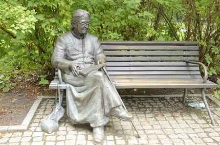 Warsaw, Poland - July 29, 2018: Bench Sculpture for Father Jan Twardowski,  a poet and Catholic priest in Warsaw, Poland. Editöryel