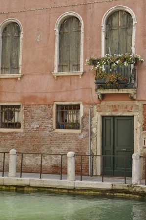 Green wooden shutters on wall at canal in Venice, Italy.
