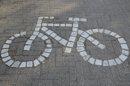 Traffic sign made with white stones for bikeway on road in Brugge, West Flanders, Belgium.