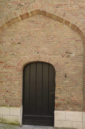 Wooden door on brick wall in Street of Brugge, West Flanders, Belgium.