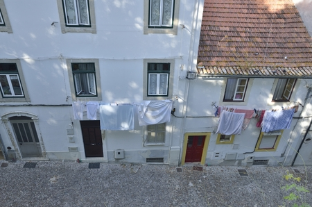 Hanging clothes at the facade of houses in cobblestone street in the old town of Coimbra, Portugal. Stock Photo