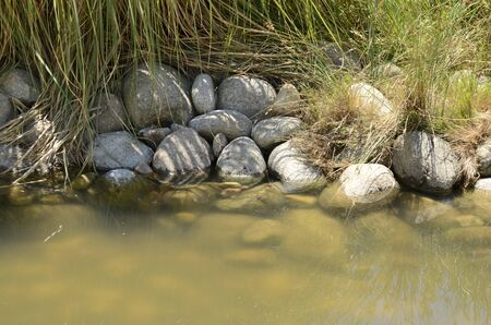 Big stones beside waterway at park located in Madrid, the capital of Spain.