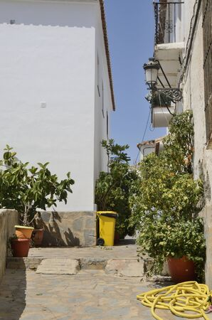 Plant pots at whitewashed alley in Casares, a  mountain village of Malaga province, Andalusia, Spain. 版權商用圖片