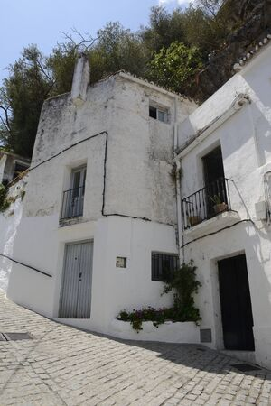 Old house at white alley sloped in Casares, a  mountain village of Malaga province, Andalusia, Spain.