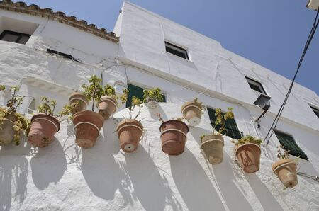 Clay pots on whitewashed wall  in Casares, a  mountain village of Malaga provicne, Andalusia, Spain.