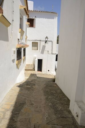 Pedestrian cobblestone alley in Casares, a mountain village of Malaga province, Andalusia, Spain.